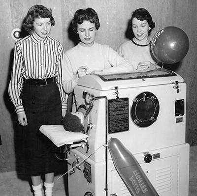 Three women next to a mini Iron Lung