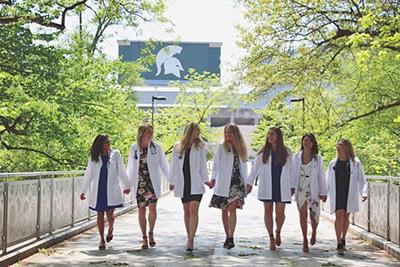 Graduates in front of football stadium